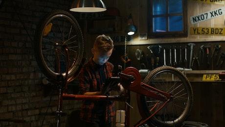 Teen boy watching tutorial to repair the bicycle