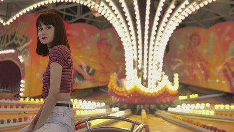 Teenage woman sitting in a mechanical fair game with the lights on