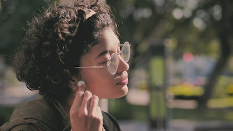 Teenager putting on headphones in the park