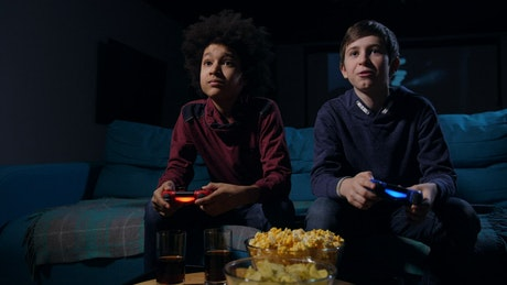 Teens playing a video game in a dark living room
