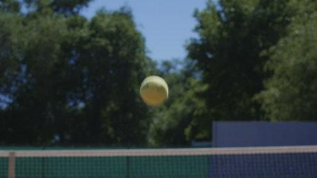 Tennis ball flying over the net