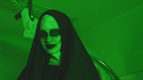 Terrifying woman disguised as a nun under a green light