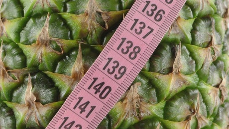 Texture of a green pineapple and a measuring tape