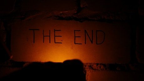 """The end"" written on the wall lit with a match"