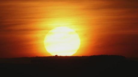 The sun hiding on the horizon during sunset