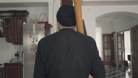 Thief with baseball bat looks around house