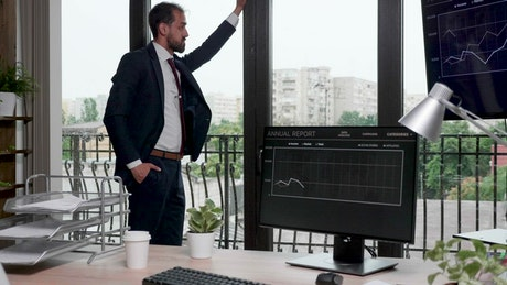 Thinking businessman stands by windows in office