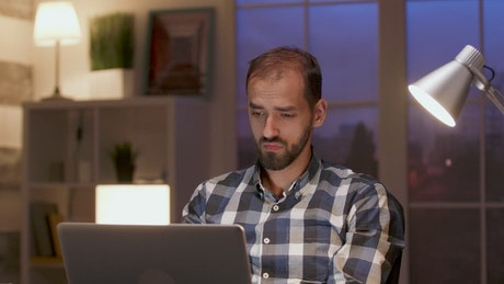 Thinking man works late and stretches in home office