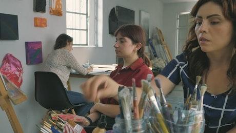 Three artist girls working in a painting workshop