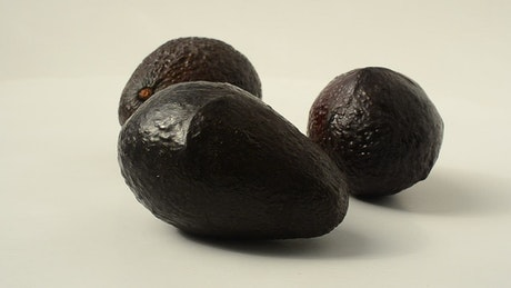 Three avocados rotating on a white background