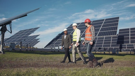 Three engineers working on a solar panel field