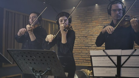 Three expert violinists playing together in a studio