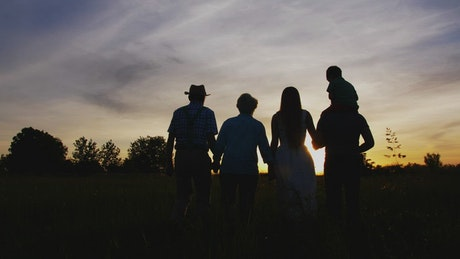 Three generations walking together at sunset
