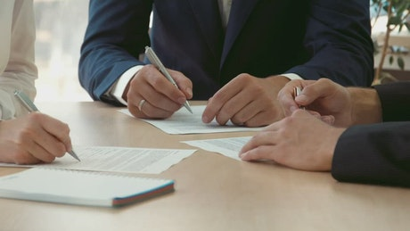 Three persons signing contracts