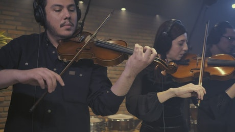 Three violinists playing together in a recording studio