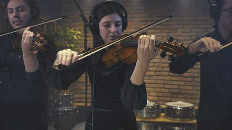 Three violinists recording a song in a studio