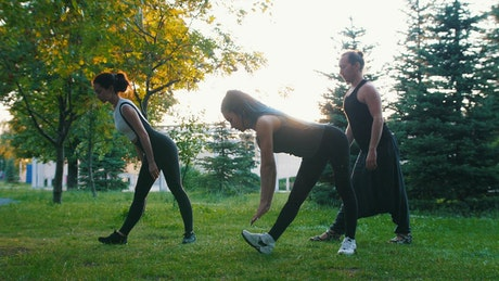 Three women exercising on the grass in a park