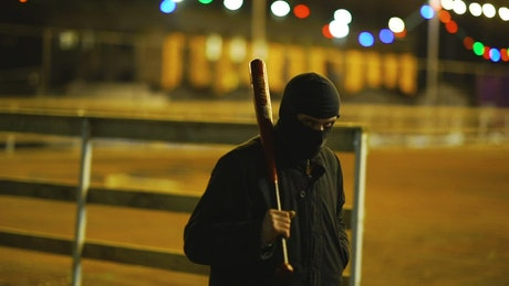 Thug with balaclava walking with a bat