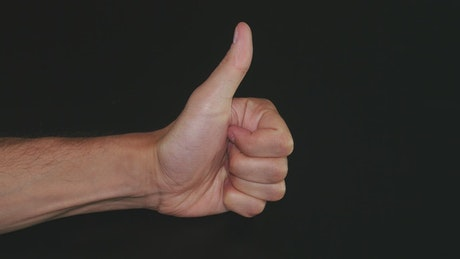 Thumbs up against a dark background