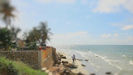 Tilt shift of people walking on windy beach