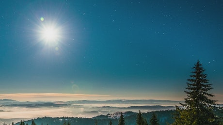 Time-lapse of a bright moon seen from the mountain