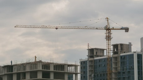 Time lapse of workers and construction cranes