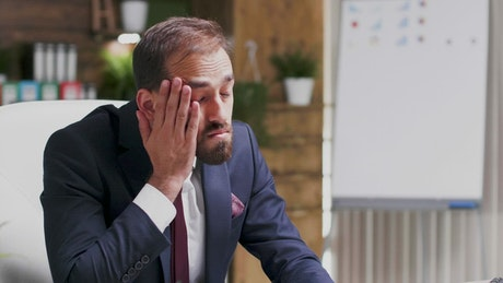 Tired businessman takes his face