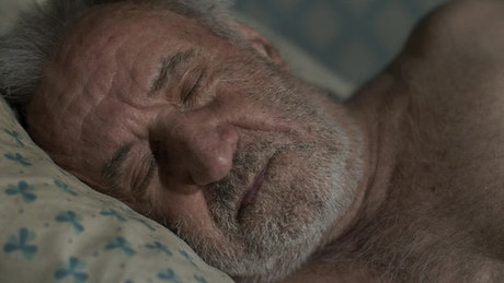 Tired old man wakes up in his bed