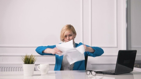 Tired woman fed up with work throws papers in air