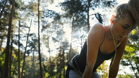 Tired woman jogging outside stops for a breath