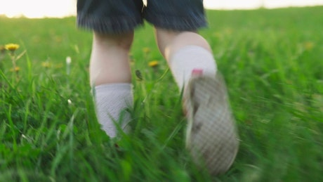 Toddler running through grass