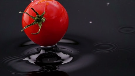Tomato falling into black water