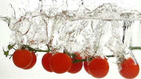 Tomatoes falling through water