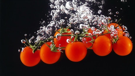 Tomatoes falling through water, black background