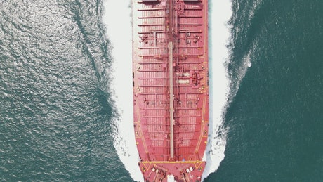 Top aerial shot of a cargo ship sailing in sea