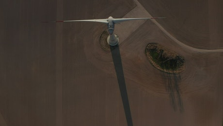 Top aerial shot of a wind turbine spinning