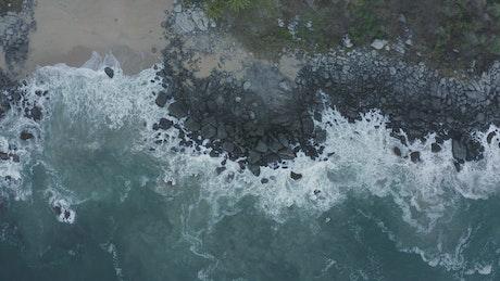 Top aerial shot of seashore with rocks
