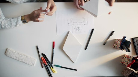Top view of creative hands working on paper models and diagrams