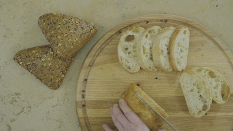Top view of hands cutting fresh bread on wood board