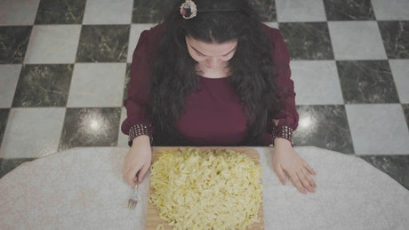 Top view of obese woman eating huge dish of pasta