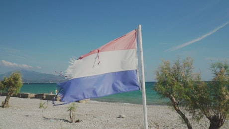Torn red, white and blue flag waving on a beach