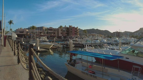 Touring a touristy and sunny port with boats and sailboats