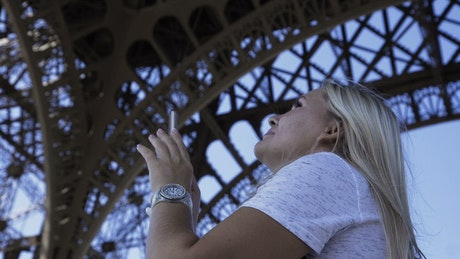 Tourist making a panorama below the Eiffel tower
