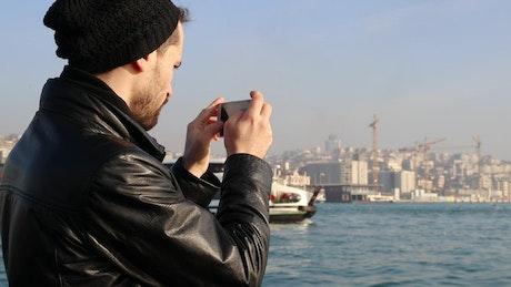 Tourist taking photos to a passenger boat