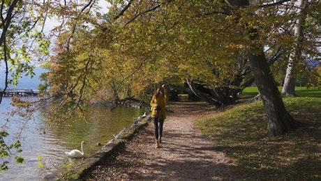 Tourist woman walking along the lake shore