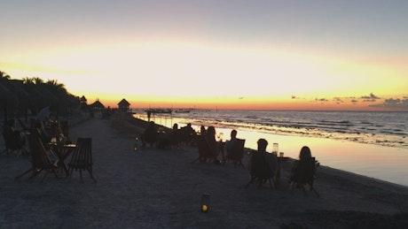 Tourists at a beach bar watching at sunset