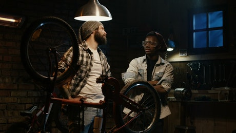 Tow young man talking in a bicycle repair shop