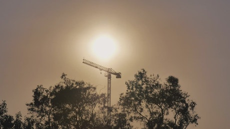 Tower crane during sunset seen in the distance