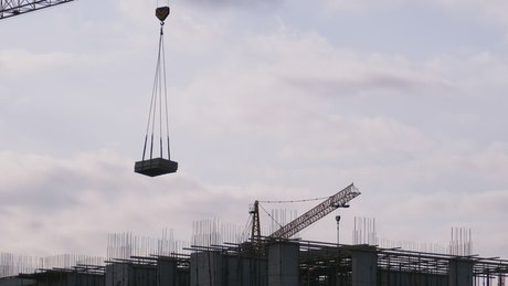 Tower crane with load on a construction site