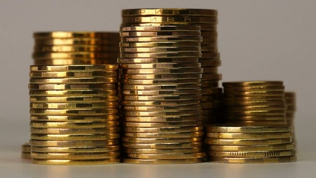 Towers of golden coins rotating on a gray background
